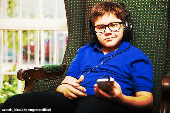 tween in an armchair, at home, listening to a podcast